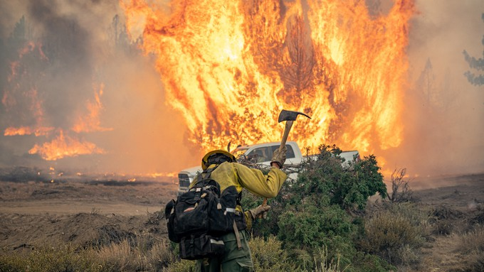 Image caption: A firefighter battles the Dixie Fighter, a massive blaze started by PG&E equipment.