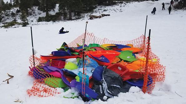 Image caption: A sled corral full of broken plastic sleds at Fallen Leaf Lake Hill.