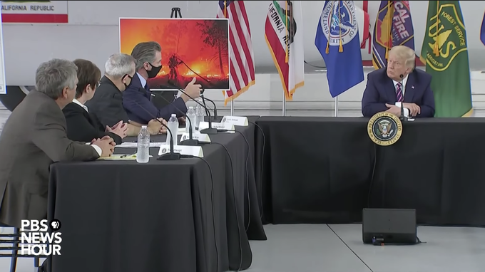 Image caption: President Donald Trump sits across from California Governor Gavin Newsom at a press conference on the state's increasingly destructive fire season. Screen shot from the PBS NewsHour YouTube channel.